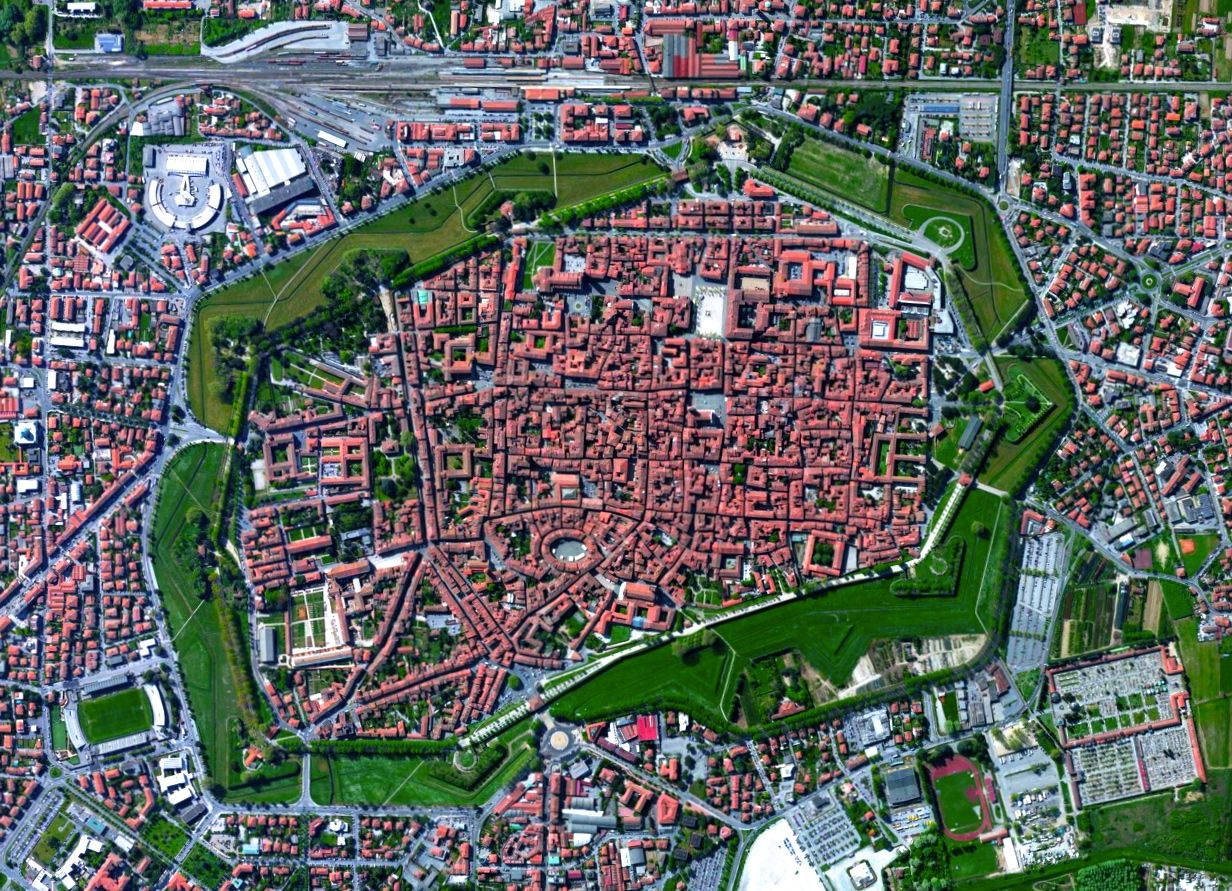Lucca at Tuscany, Italy - photo by dailyoverview;  Lucca is a city and commune in Tuscany, Italy. The city walls, constructed during the Renaissance era, have remained intact as the city expanded. As the walls lost their military importance, they became a pedestrian promenade that encircles the old town, although they were used for a number of years in the 20th century as a track for racing cars.