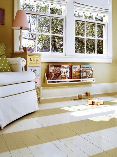 Pained floors, a comfy chair and a spice rack book shelf look sweet in a playroom or nursery.