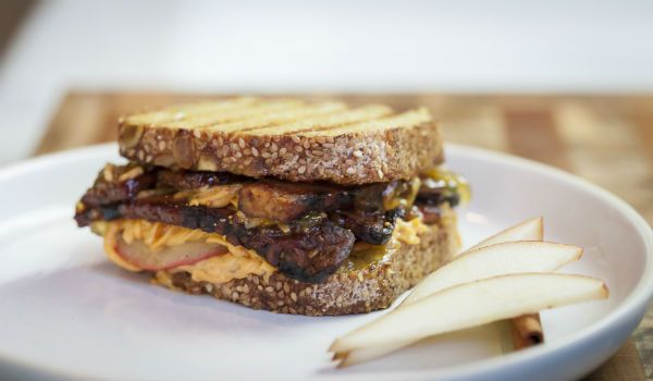 Jason Wrobel funks up the traditional grilled cheese with a dairy-free vegan tip that includes sliced pear, fig jam, and tempeh bacon.