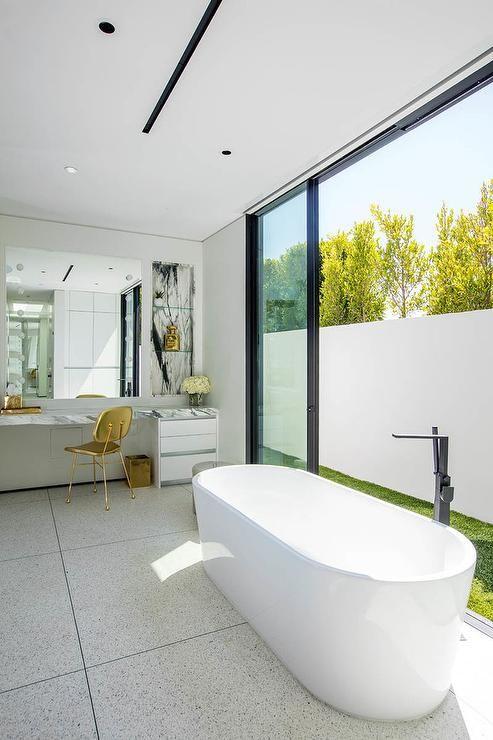 Stylish contemporary bathroom features an oval freestanding bathtub on