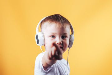 little boy listening a music in a headphones. Kid in earphones, show finger to vamera against yellow background. , #Affiliate, #headphones, #Kid, #music, #boy, #listening #Ad