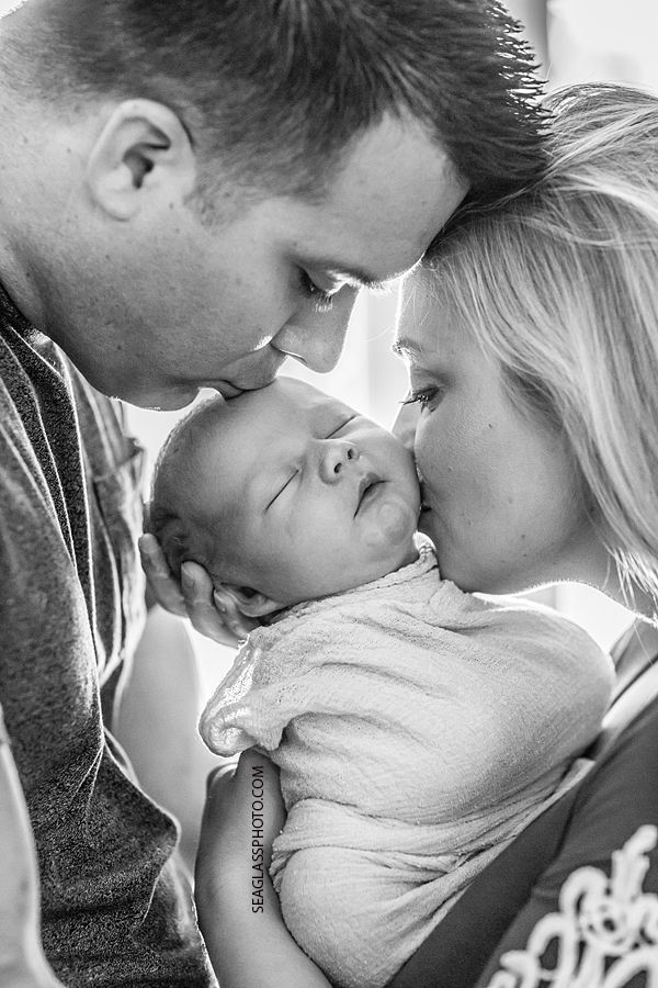 Close up black and white photo of mom and dad kissing their newborn son during new born session in Vero Beach Florida