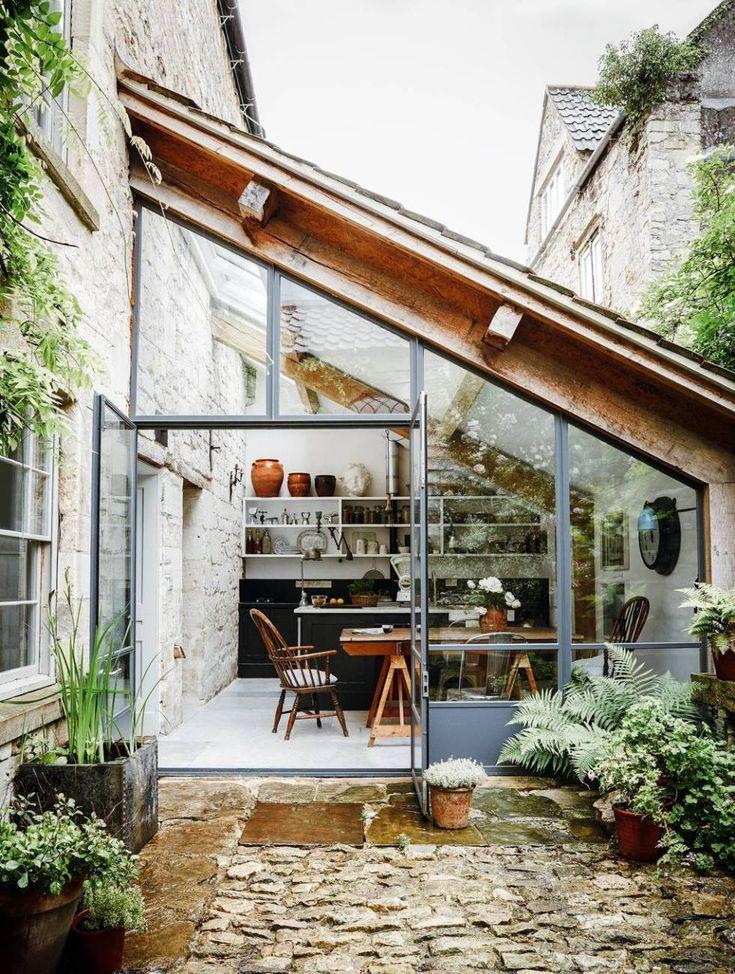 Photo of Küche und Essbereich, eingerahmt von einer großen Glaswand, öffnen sich zu einem Innenhof in einem …