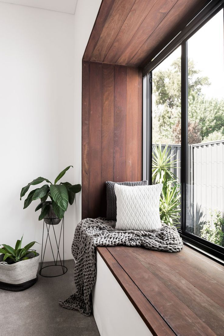 This modern bedroom has a wood framed window seat that overlooks the ...