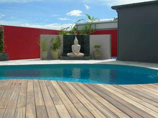 Belle piscine à forme libre et sa terrasse en bois pour un espace de
