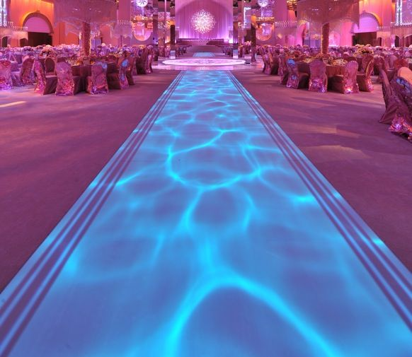 Blue water lighting creating a rippling design on the runner, contrasted by pink uplighting and a persian lace gobo.