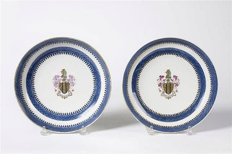 """Each painted in famille rose enamels and gold with the armorial and motto """"BEATA PETAMUS ARVA,"""" within trellis diaper and spearhead borders. Diameter 10 1/2 inches.Provenance: Property of a midwestern collection.Literature: David Sanctuary Howard, """"Chinese Armorial Porcelain,"""" vol. I, p. 727, V14."""
