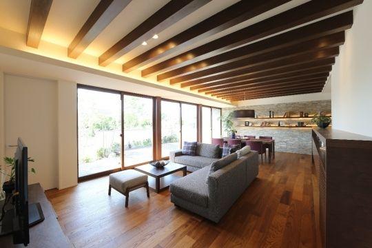 半あらわし梁の天井が木のぬくもりを感じさせるリビング そして連続大開口 フルフラットによりつながるウッドデッキの空間はアウトドアリビングとして四季を感じる家族の憩い