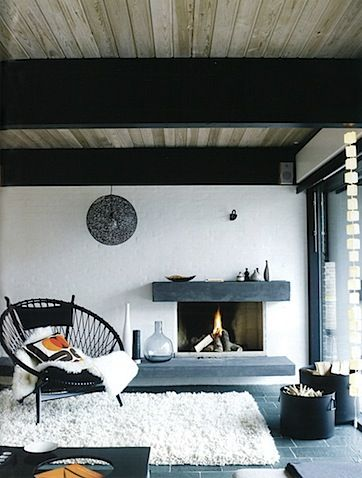 Elle uk decoration. Living room with built in fireplace, white walls, and vaulted ceilings.