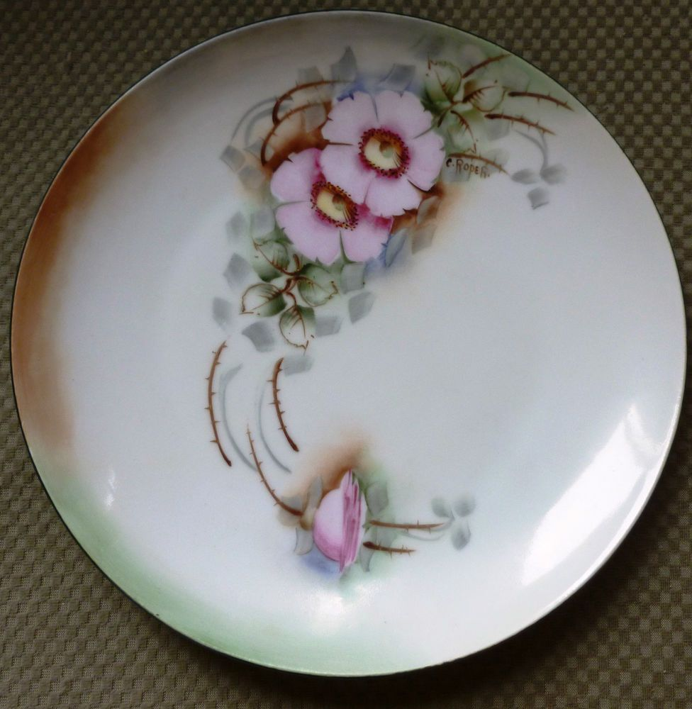 This is a lovely plate~Hand painted~With pink flowers that have cream-colored and green centers~with pastel green leaves and brown branches and thorns There are strokes of blue and gray that compliment the pink and green~The background is cream-colored with areas of light brown and green~Artist signed Circa 1918-1928