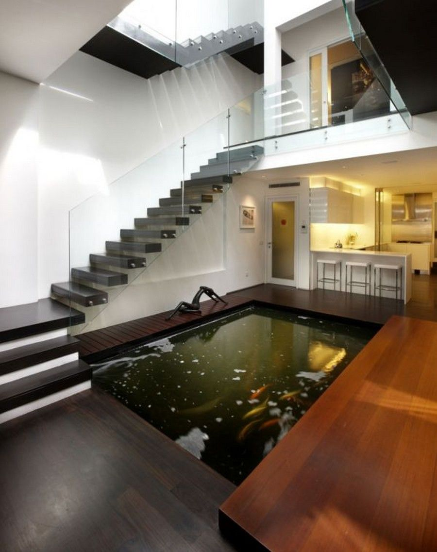 Modern indoor koi pond of contemporary home with stained for Modern fish pond ideas