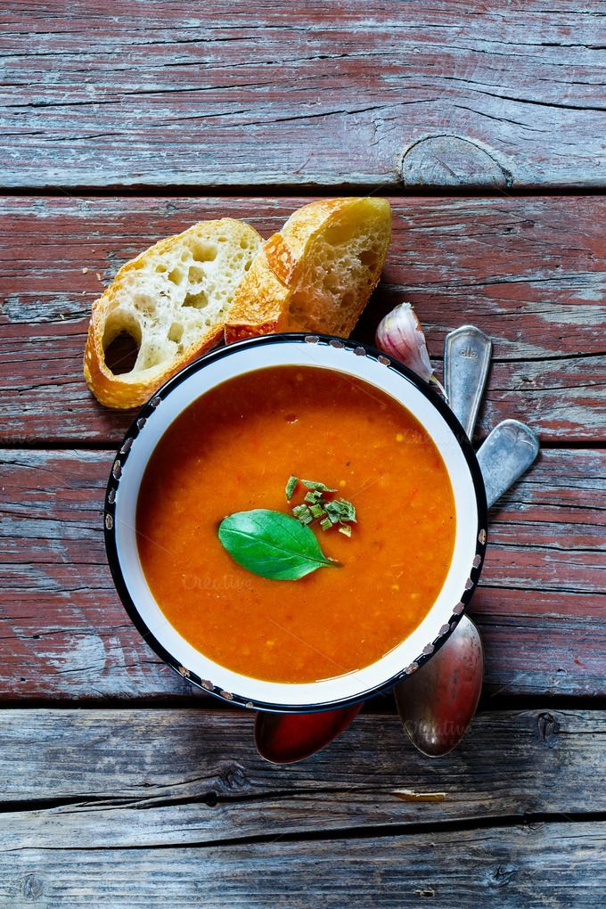 #Tomato soup Gazpacho  Old table with rustic metal bowl of tomato soup Gazpacho fresh baguette garlic and basill on wooden background top view.