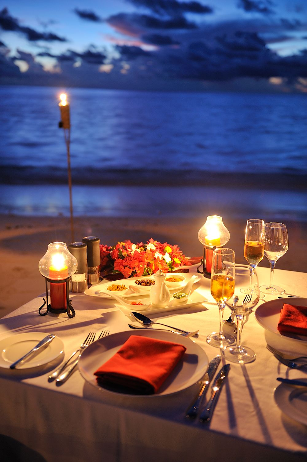 Romantic Room Setting: Set Up A Nice Table On The Beach With Candles And Torches