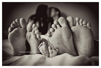 Baby and parent's feet photo. So the baby is smashed between their legs down by their feet. Looks comfy.