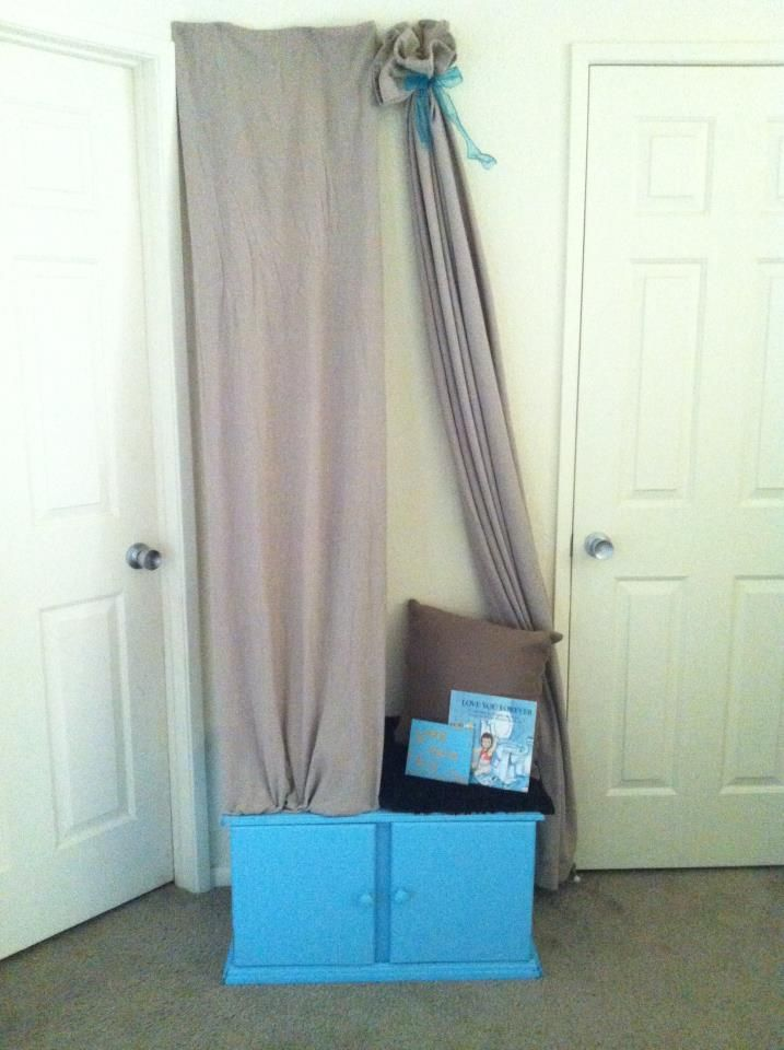 """the kids new book reading area I made for them using spray paint, an old bottom to a gun cabinet, some old curtains, a blanket, and I even made a little sign for it that says """"Book Nook sit and read awhile""""- all the books get stored underneath so to maximize space :)) and they can wrap the other curtain around them while reading for a more cubby hole approach."""