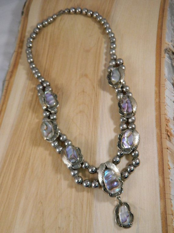 This is a vintage 1960s Native American sterling silver squash blossom necklace. This necklace is big, bold and powerful! Its 20 long, handworked and definitely and older, true Indian piece. It has eight oval-shaped abalone stones that shimmer with shades of purple, pink, green and cream. Each stone is set in an ornate frame. The six in the main body of the necklace have a feather along the side and gorgeous swirled metal work on the other side. The center, largest stone has two feathers at…