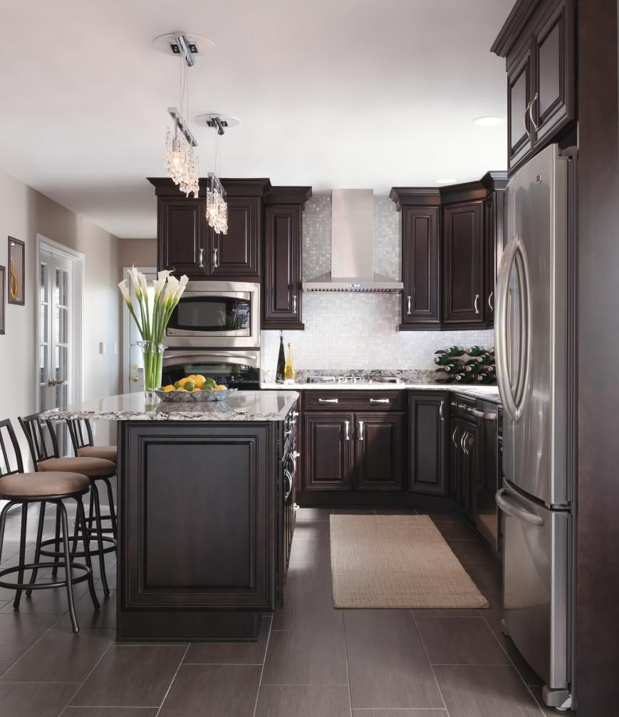 Glamorous touches like a stainless hood and crystal for Chocolate kitchen cabinets with stainless steel appliances