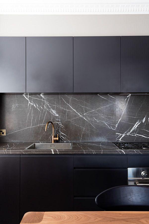 Cocina oscura con encimera y salpicadero en mármol negro Mesa de
