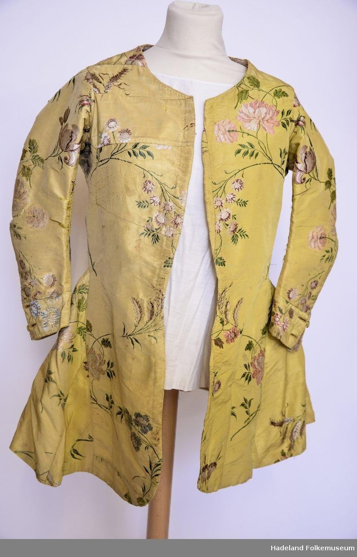 Trøye/jakke kvinne. Gul silkebrokade med brosjering, blomstermotiv. kort modell. Sammensatt av stoffbiter, trolig fra eldre drakt. Foret m linstoff i lerretsbinding. Innsvinget i livet, med utskrådd avslutning. Lange ermer, uten krage eller slag.