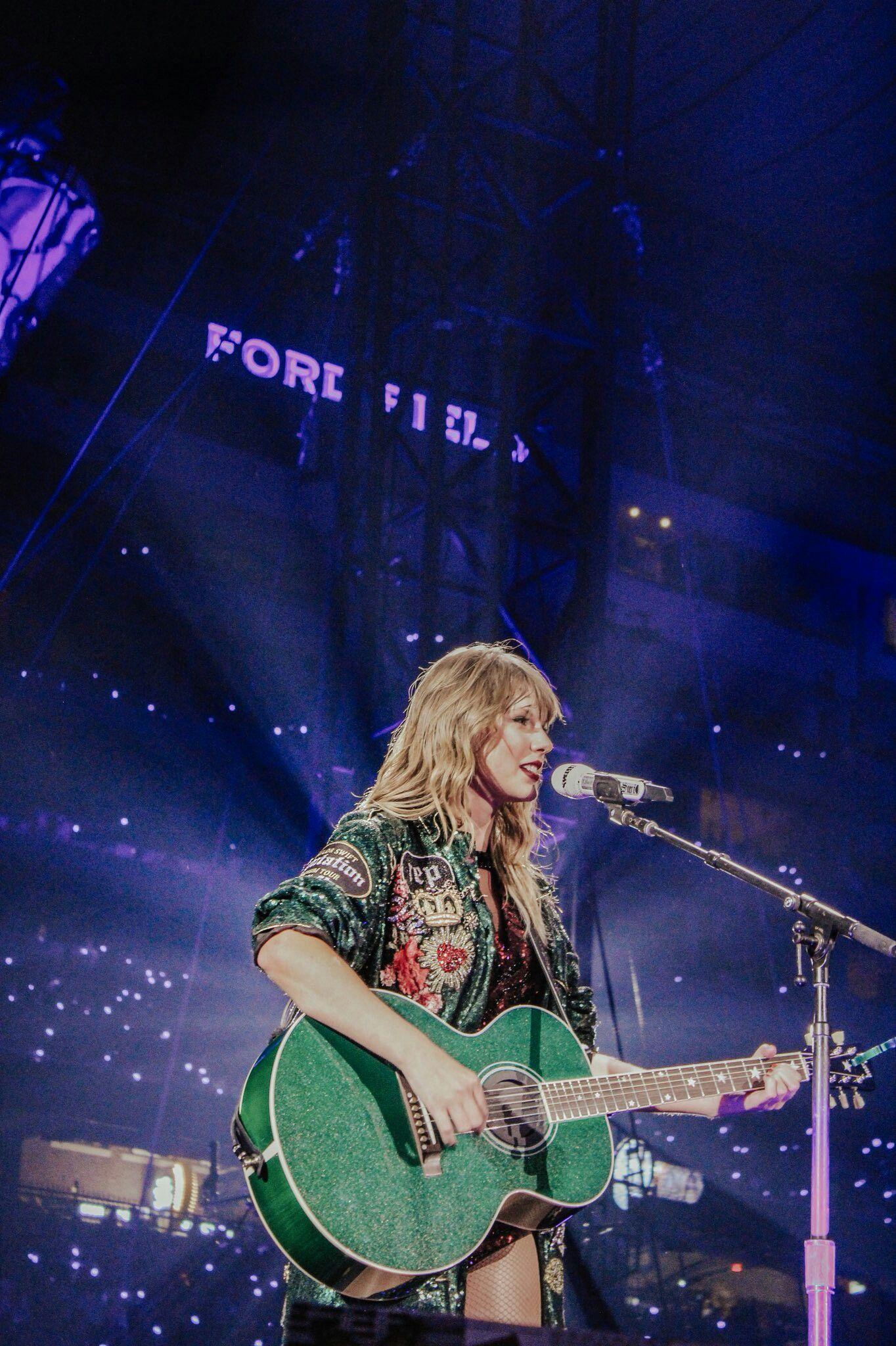 Taylor Swift, cantora e compositora norte-americana em show com seu violão jumbo na cor verde e tampo verde com glitter.