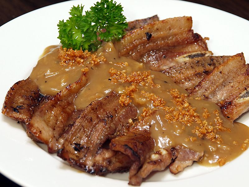 """Grilled Pork ala Pobre  The word """"a la pobre"""" may sound like a Spanish dish but it is just a term used for a thick brown gravy sauce with lots of crispy fried garlic bits. The word """"a la pobre"""" means """"the poor"""", it is a common definition used for the dishes that are served by peasants during the Spanish regime in the Philippines."""