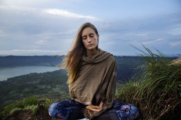 woman meditating on mountain against sky  meditate