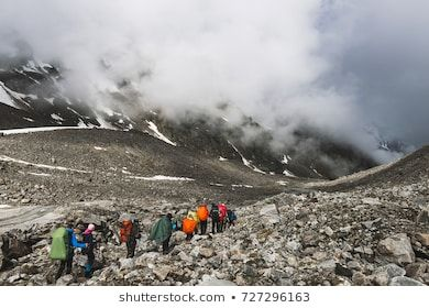 ELBRUS REGION, RUSSIA - JUNE 22, 2017:  Group of tourists goes on a hike in the Elbrus region and follow each other. Dramatic view with snowy mountain peaks covered in clouds #active, #activity, #adventure, #autumn, #background, #backpack, #beautiful, #caucasus, #climber, #climbing, #elbrus region, #expedition, #far, #glacier, #group, #haze, #healthy, #hike, #hiking, #hill, #horizon, #ice, #journey, #kamchatka, #landscape, #large, #many, #marathon, #mountain, #nature, #peak, #people, #person, #r