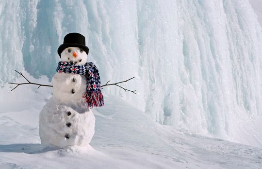 Snowman near frozen waterfall, Alaska (© Alaska Stock/Alamy)