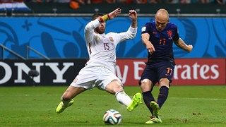 Arjen Robben of the Netherlands shoots and scores his teams second goal as Sergio Ramos of Spain defends