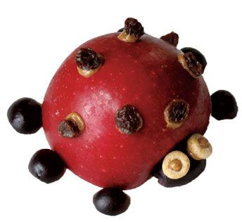 Apple ladybug snack with peanut butter, blueberries, raisins, and cherrios