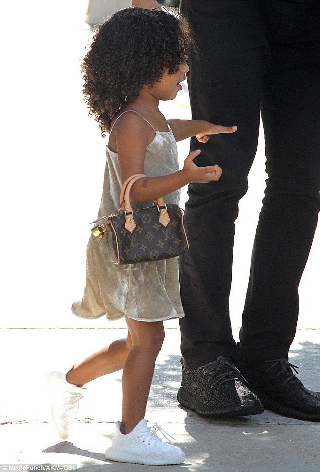2a10f910a North West carried a miniature Louis Vuitton bag on her arm as she stepped  out in New York on Thursday