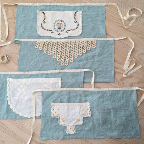 Handmade linen cafe aprons adorned with vintage lace and embroidered findings. Each apron is one of a kind. long twill ties will fit a range of sizes from 3years to 13. Most of the trim pieces were fashioned into pockets on these darling and useful aprons. Please select your color choice and then choose the style numbered from top to bottom after previewing the photos.