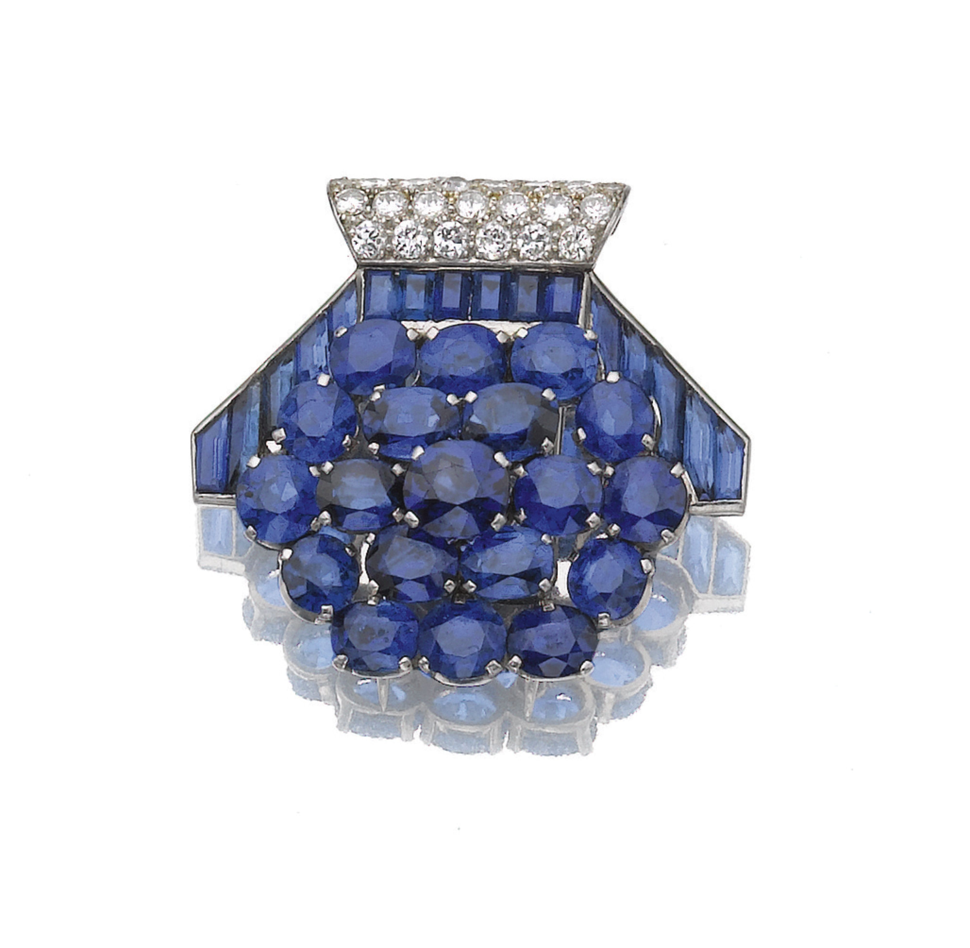 Sapphire and diamond clip, Cartier, circa 1930 Of stylised shield design, set with oval and calibré-cut sapphires, accented with a pavé-set brilliant and single-cut diamond motif, signed Cartier London, numbered.