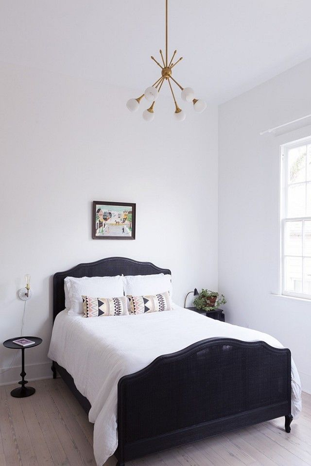 Minimalist Inspired Bedroom With A Retro Chandelier And A Vintage Bed Frame