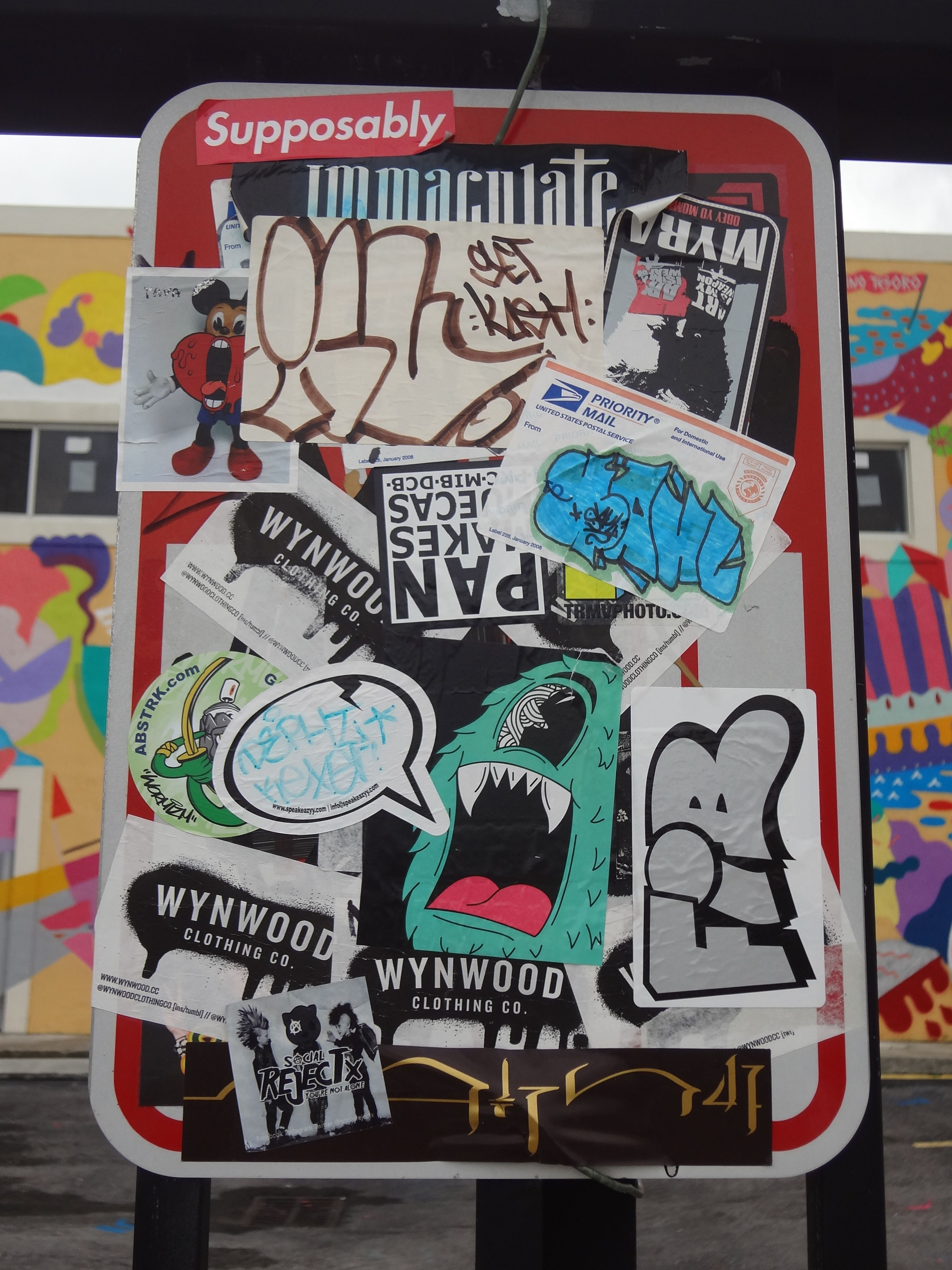 Sticker bombed street sign outside a shoe warehouse in
