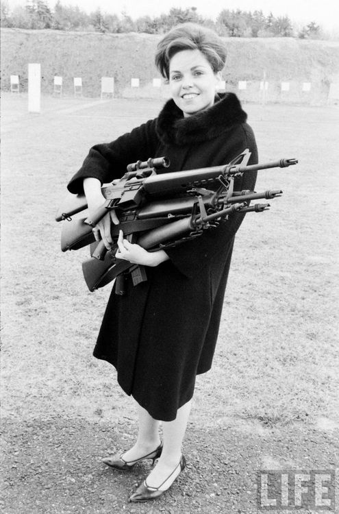 A mother with a bouquet of assault rifles. Perhaps for her son to play with. Photo by Arthur Rickerby, Life magazine, 1963.