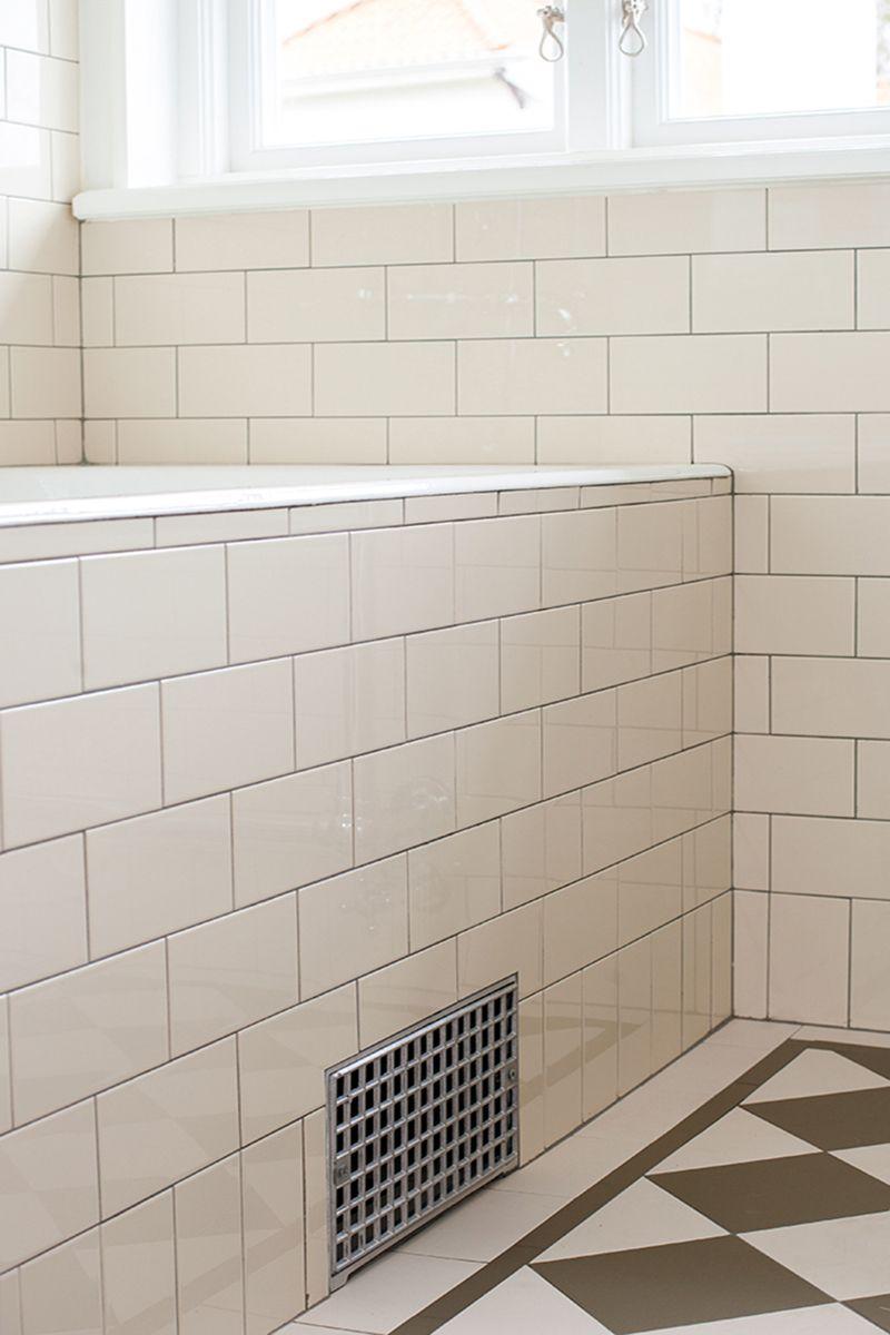 Badrum i 20-talsstil med halvkaklade väggar med ett avslut med en ...