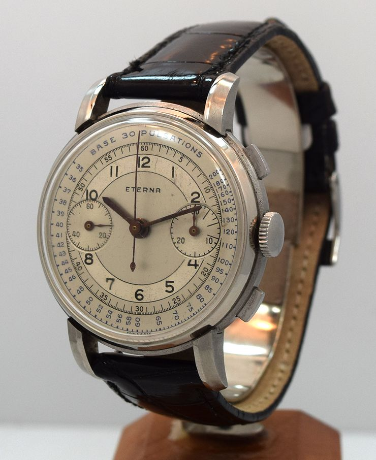 A 1950's vintage Eterna 2 Register Chronograph stainless steel watch with a two-tone silver and gray dial with black Arabic numerals and blue Arabic outer tachometer numerals. This timepiece is 37mm wide and is fitted with a manual caliber 703 R movement. (Store Inventory # 10019, listed at $2650).  #eterna #chronograph #vintage #watch #classic #watches #stawc