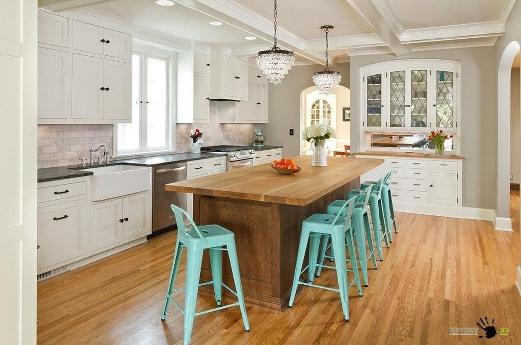 Simply wooden kitchen island with green dining stools and enchanting chandeliers…