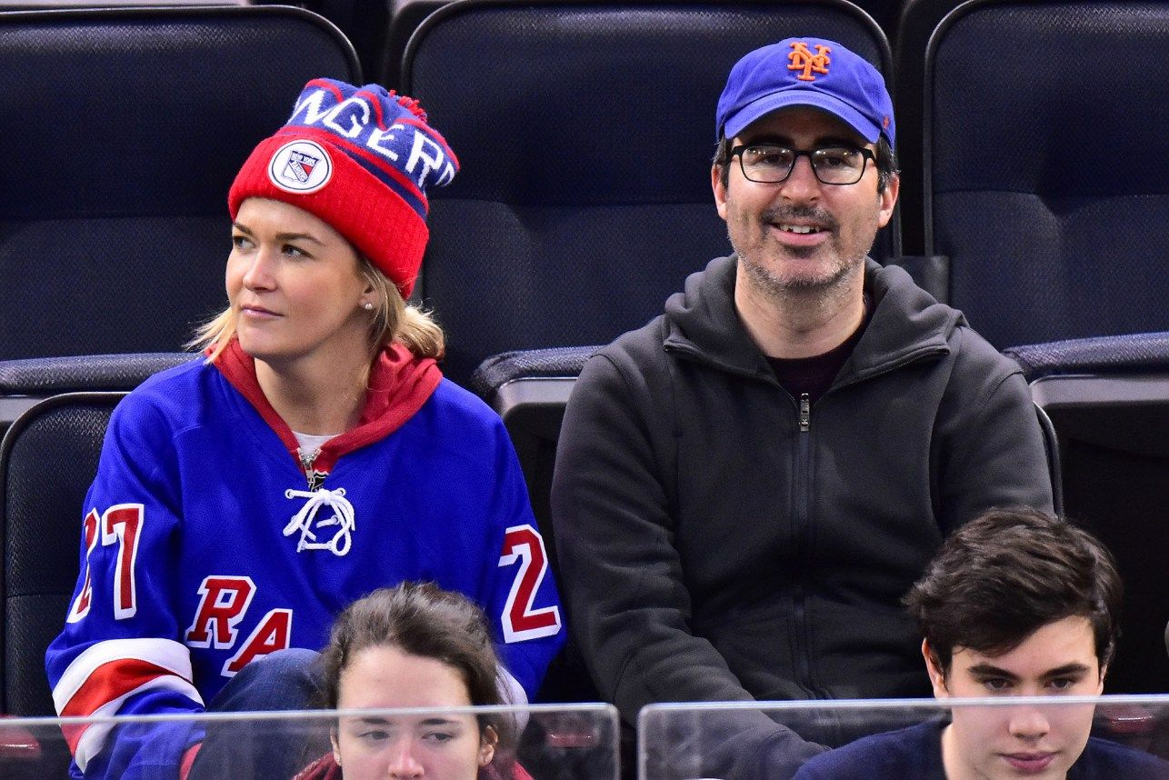 John Oliver And Wife Kate Norley Attend The New York Rangers Game At Madison Square Garden On