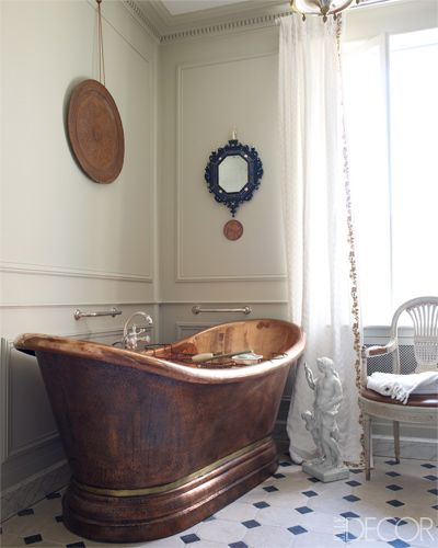 A bathroom's copper tub and fittings are by Herbeau, the 1940s chair is by Jansen, and the linen for the curtains is by Chelsea Textiles.