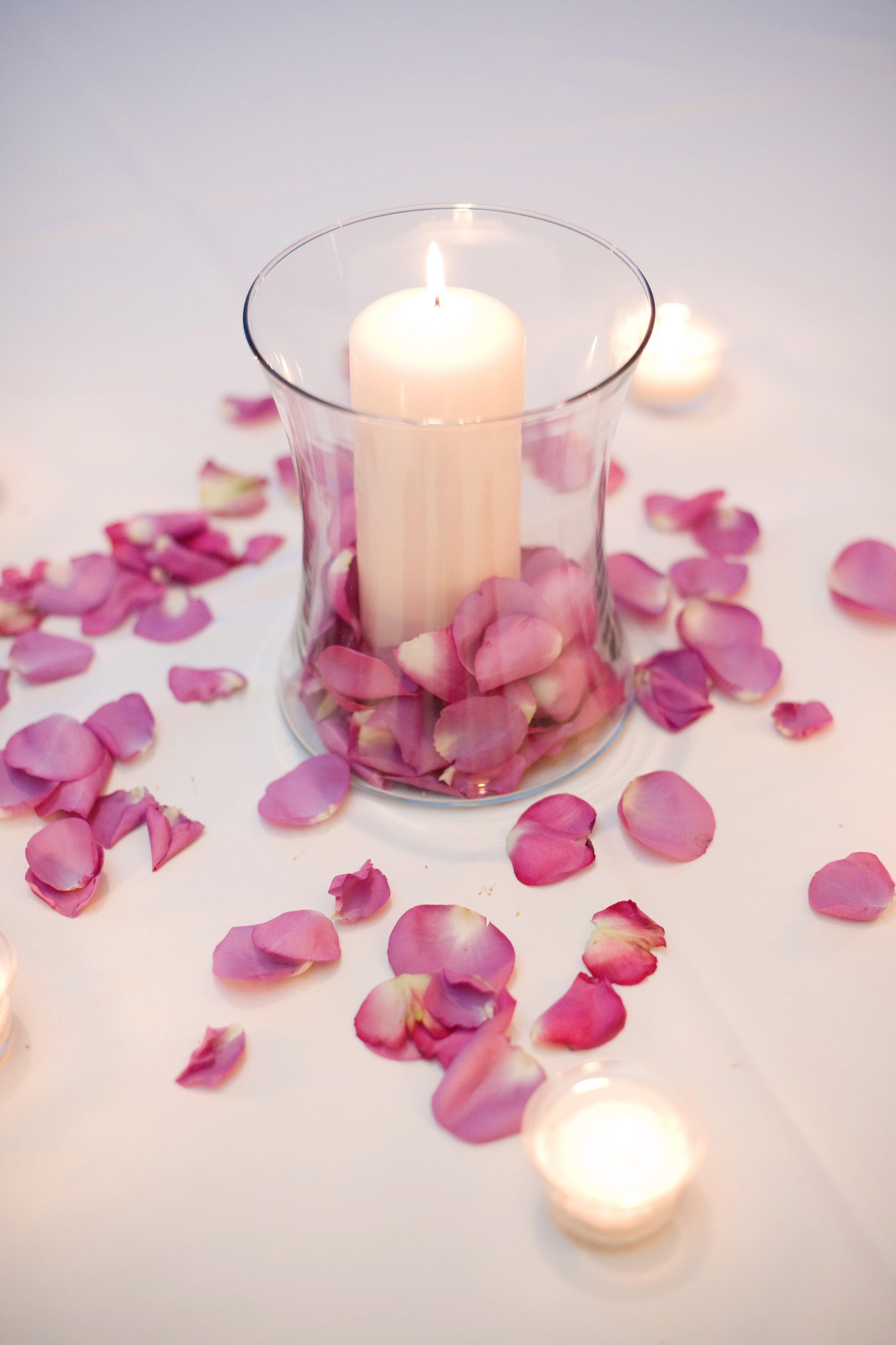 guest table centerpiece with pillar candle  votive candles  and cool water rose petals scattered