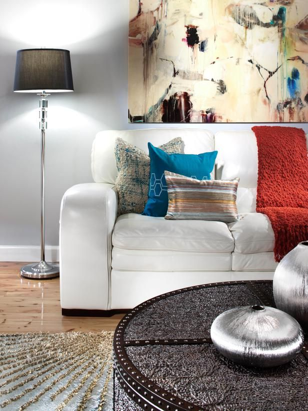 An all-white sofa gets a bit of character with the addition of colorful textured pillows and modern wall art.