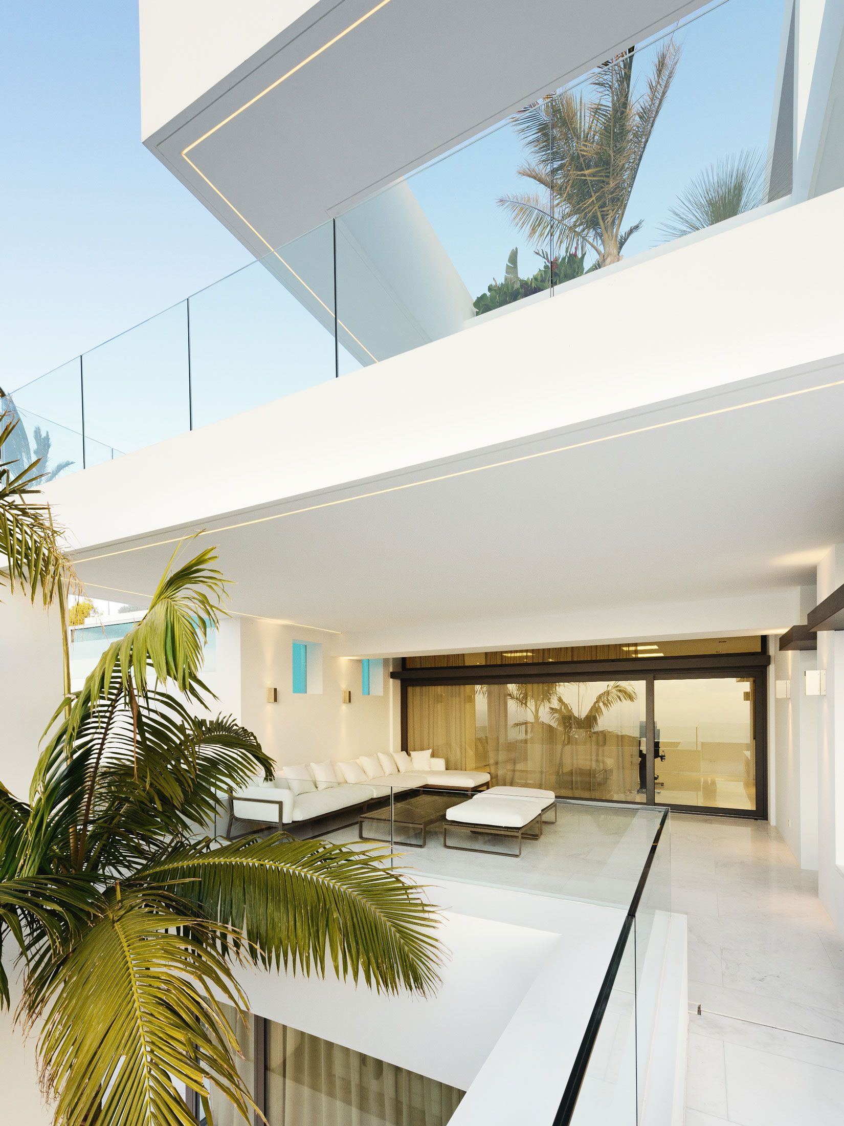 Breathtaking Cliff house design in white scheme featuring exterior living space with marble floor glass wall and fence as well as greenery.jpg