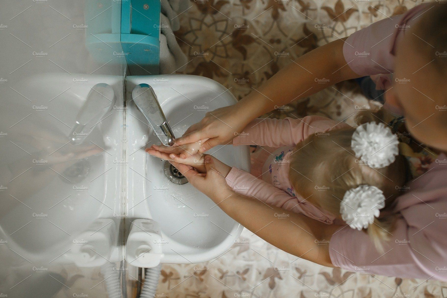 Photo of Toddlers wash their hands in a washstand in kindergarten. Concept of hygiene, pr…