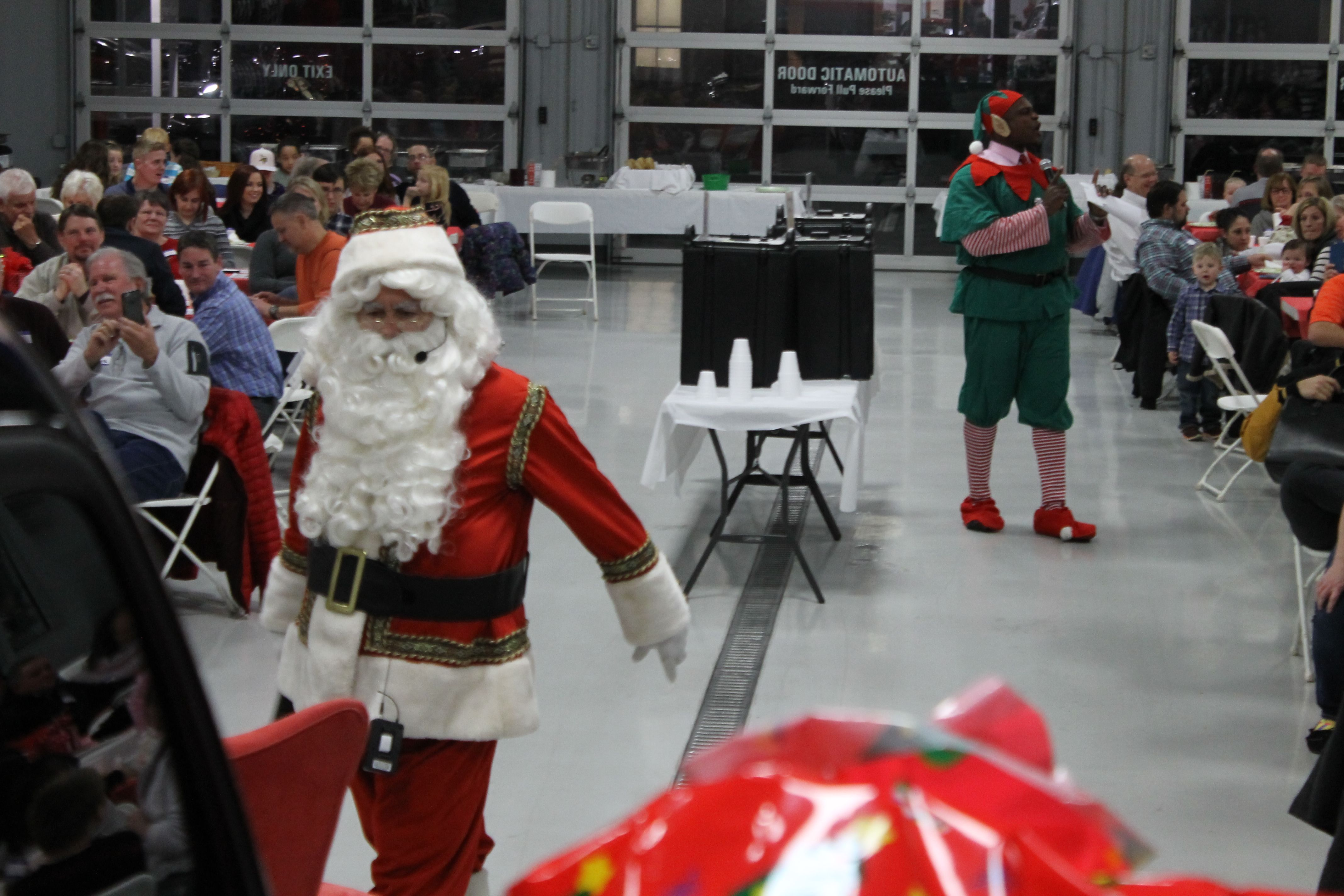 Santa walks past tables filled with employees of Wilson