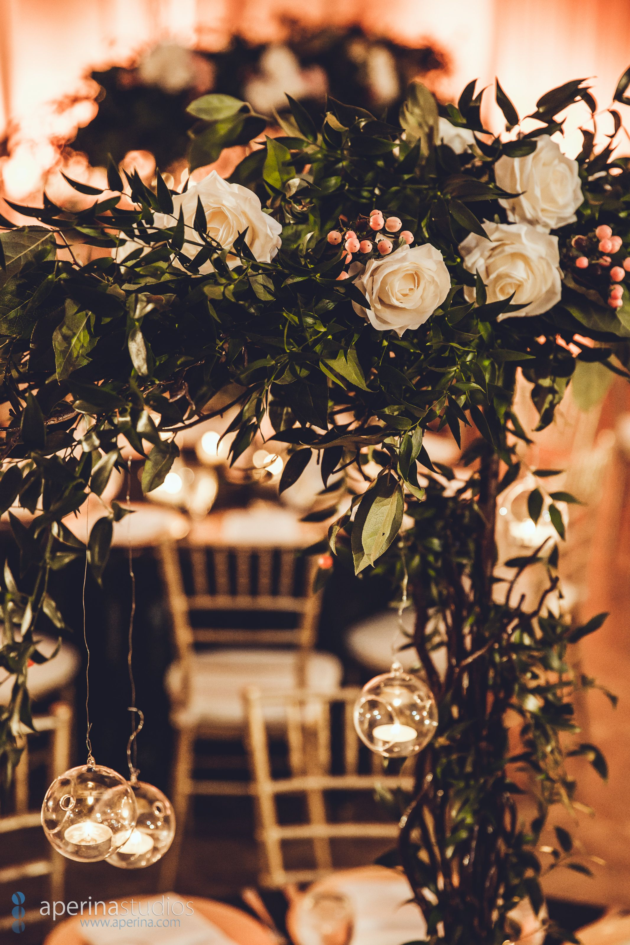 Gorgeous greenery and white roses with hanging tea lights at the