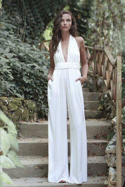 5f074b849b9c Stunning white halter style jumpsuit with a deep V-neckline and loose wide  leg pants. Belted at the waist for a flattering silhouette.