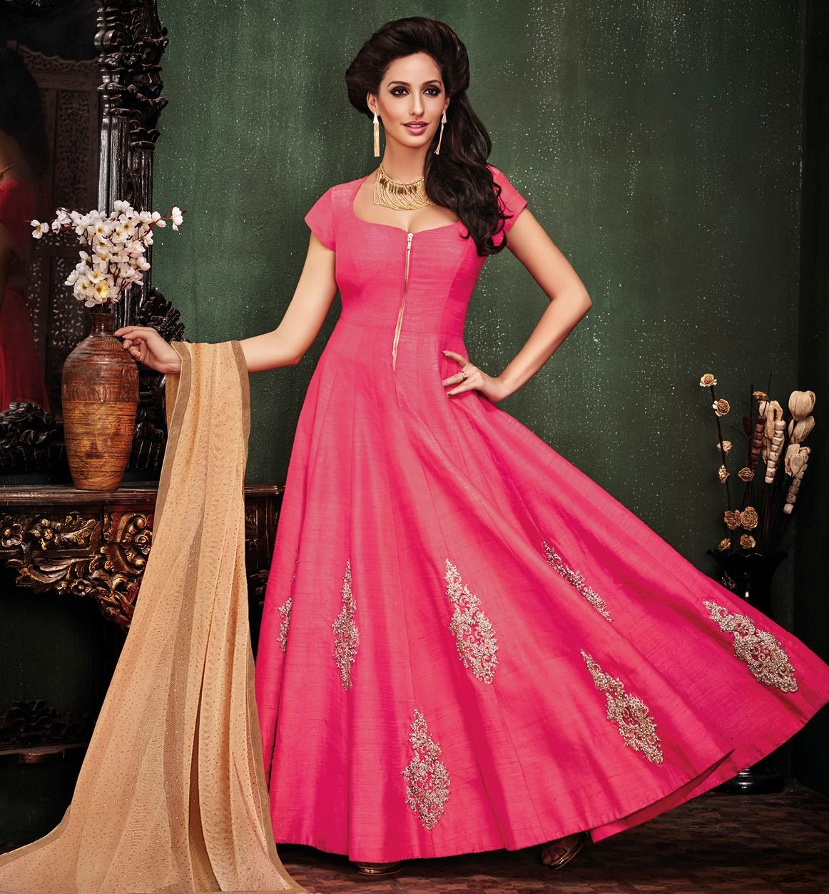 This raw silk Anarkali is embellished with applique work at