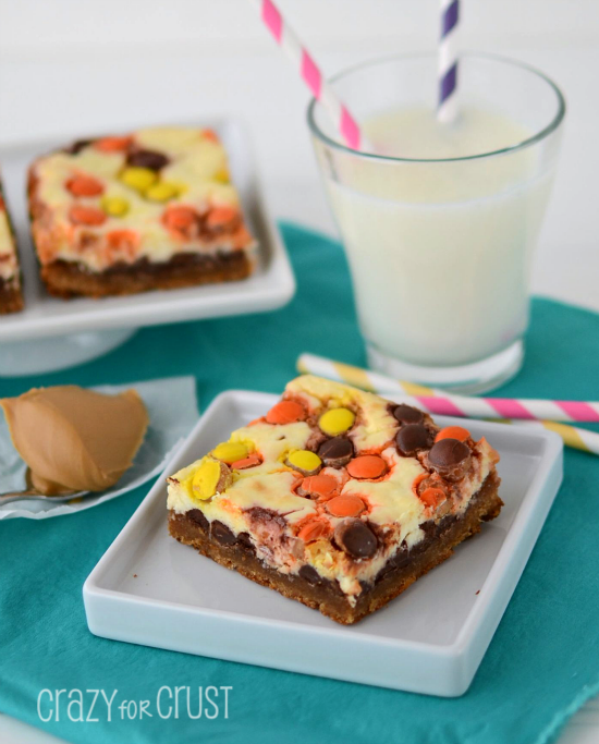 Peanut Butter Cookie Cheesecake Bars by www.crazyforcrust.com | A peanut butter cookie base topped with chocolate chips, cheesecake, and Reese's Pieces. One of the best cheesecake bars yet! #Reeses #cheesecake #cookie